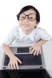 Bambina sveglia con i vetri facendo uso del computer portatile Fotografia Stock Libera da Diritti