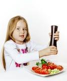 Bambina sveglia con il contenitore di pepe e di insalata Fotografia Stock