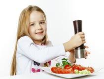 Bambina sveglia con il contenitore di pepe e di insalata Immagini Stock Libere da Diritti