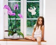 Bambina sveglia con il fiore che si siede sul davanzale di nuovi wi del PVC Immagine Stock Libera da Diritti