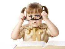 Bambina sveglia con il libro che porta i vetri neri Fotografie Stock