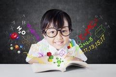 Bambina sveglia con il libro e la formula Immagine Stock