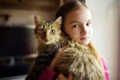 Bambina sveglia con il suo gatto a casa Bambino adorabile che tiene il gattino dell'animale domestico del het fotografia stock