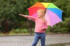 Bambina sveglia con l'ombrello luminoso sotto pioggia fotografia stock