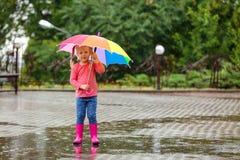 Bambina sveglia con l'ombrello luminoso sotto pioggia fotografia stock libera da diritti