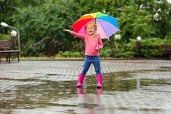 Bambina sveglia con l'ombrello luminoso sotto pioggia immagine stock