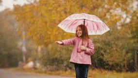 Bambina sveglia con l'ombrello sotto pioggia archivi video