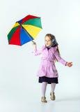 Bambina sveglia con l'ombrello variopinto immagine stock libera da diritti