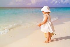 Bambina sveglia con la borsa che cammina sulla spiaggia Fotografia Stock