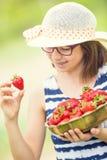 Bambina sveglia con la ciotola piena delle fragole fresche Ragazza teenager pre- con i vetri ed i denti - ganci dentari Fotografia Stock