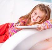 Bambina sveglia con la compressa Fotografia Stock