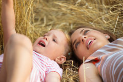 Bambina sveglia con la giovane madre che si trova nel giacimento di grano Immagine Stock Libera da Diritti