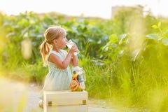 Bambina sveglia con la limonata bevente dei capelli biondi all'aperto La frutta della disintossicazione ha infuso l'acqua condita immagini stock