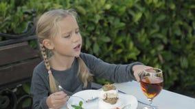 Bambina sveglia con le trecce che mangia dessert stock footage