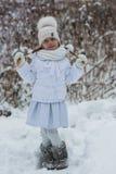 Bambina sveglia con un giorno nevoso di camminata di due trecce nel parco in un vestito bianco Fotografia Stock Libera da Diritti