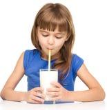 Bambina sveglia con un vetro di latte fotografie stock