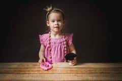 Bambina sveglia con uno specchio e una spazzola Fotografia Stock