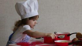 Bambina sveglia del ritratto vestita come alimento del cuoco del cuoco unico stock footage