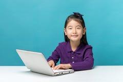 Bambina sveglia dell'Asia che gode del computer portatile su fondo blu Fotografia Stock Libera da Diritti