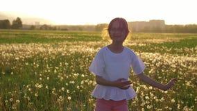 Bambina sveglia di vacanza di primavera che gira e che balla nel campo con i denti di leone divertendosi e godendo della vita pos archivi video