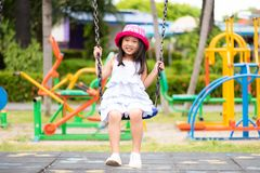 Bambina sveglia divertendosi con l'oscillazione nel parco immagini stock