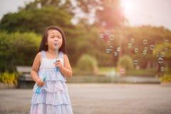 Bambina sveglia divertendosi con le bolle di sapone di salto Fotografie Stock