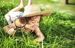 Bambina sveglia divertendosi con un magnifer fotografia stock libera da diritti