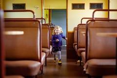 Bambina sveglia divertente che passa un vagone vuoto del treno Bambino in buona salute felice del bambino divertendosi sul viaggi fotografia stock libera da diritti