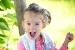 Bambina sveglia dolce all'aperto con il ritratto aperto della bocca all'aperto Immagine Stock
