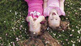 Bambina sveglia due che si trova sottosopra sulla fienarola dei prati e sui fiori che fanno la mano di bacio e di ondeggiamento d stock footage