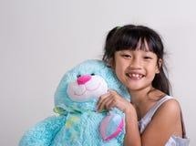 Bambina sveglia e allegra che tiene un coniglietto Fotografie Stock Libere da Diritti