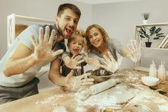 Bambina sveglia e suoi bei i genitori che preparano la pasta per il dolce in cucina a casa immagini stock