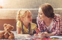 Bambina sveglia ed il suo bello disegno della madre fotografia stock libera da diritti