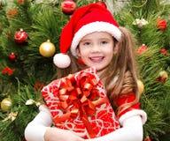 Bambina sveglia felice in cappello di Santa con il contenitore di regalo Fotografie Stock Libere da Diritti