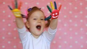 Bambina sveglia felice con le mani dipinte variopinte con i sorrisi ed il concetto di istruzione Bambino divertente con sporco in stock footage
