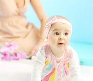 Bambina sveglia nell'ambito della vista della mamma Immagine Stock