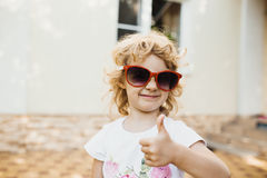 Bambina sveglia in occhiali da sole rossi Fotografia Stock