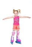 Bambina sveglia pattinare di rullo isolata su bianco Fotografia Stock