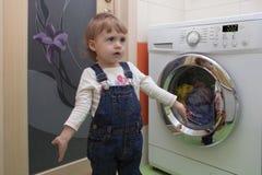 Bambina sveglia sorpresa con i vestiti che fanno lavanderia nell'interno domestico Immagini Stock