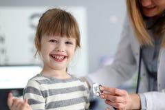 Bambina sveglia sorridente con il battito cardiaco di misurazione di medico con lo stetoscopio immagine stock libera da diritti