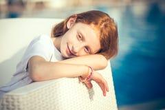 Bambina sveglia sorridente nella seduta allo stagno il giorno soleggiato fotografia stock libera da diritti