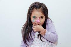Bambina sveglia spalmata di dolce sul suo fronte immagine stock libera da diritti