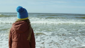 Bambina sveglia in stivali di gomma gialli che stanno sulla riva del mare e che esaminano distanza, saltante Vista posteriore stock footage