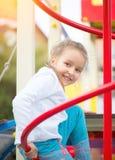 Bambina sveglia sul campo da giuoco Un ritratto all'aperto di cinque anni della ragazza che esamina macchina fotografica Fotografie Stock