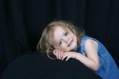 Bambina sveglia sulla parte posteriore del nero Fotografia Stock