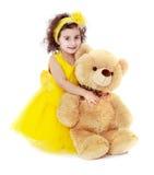 Bambina sveglia in un abbracciare giallo del vestito grande fotografia stock