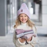 Bambina sveglia in un cappello lilla tricottato tenendo i nuovi cappelli tricottati fotografia stock libera da diritti