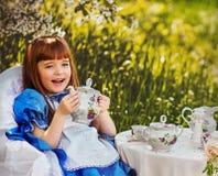 Bambina sveglia in un tè bevente del giardino della molla Immagini Stock Libere da Diritti