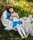 Bambina sveglia in un tè bevente del giardino della molla Fotografia Stock