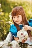Bambina sveglia in un tè bevente del giardino della molla Immagini Stock